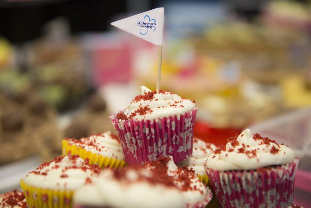 Plate of cupcakes with cream icing and red sprinkles, one with an Alzheimer's Society flag on a cocktail stick. Fundraiser for Alzheimer's Society and Dementia Friends.