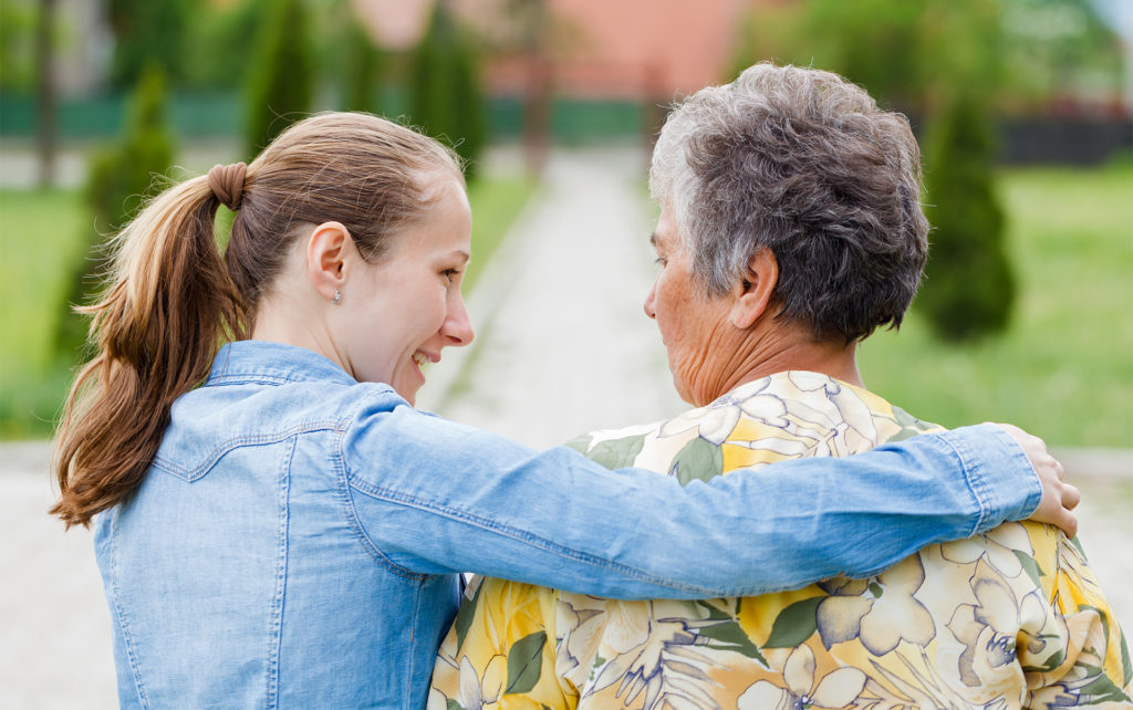 Young woman in denim shirt puts an arm around elderly woman in yellow floral shirt, back view, walking in a garden
