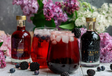 Two bulbous glasses of deep red cocktail drink, 2 bottles, one of cassis and one of framboise, with a vase of lilac blooms behind