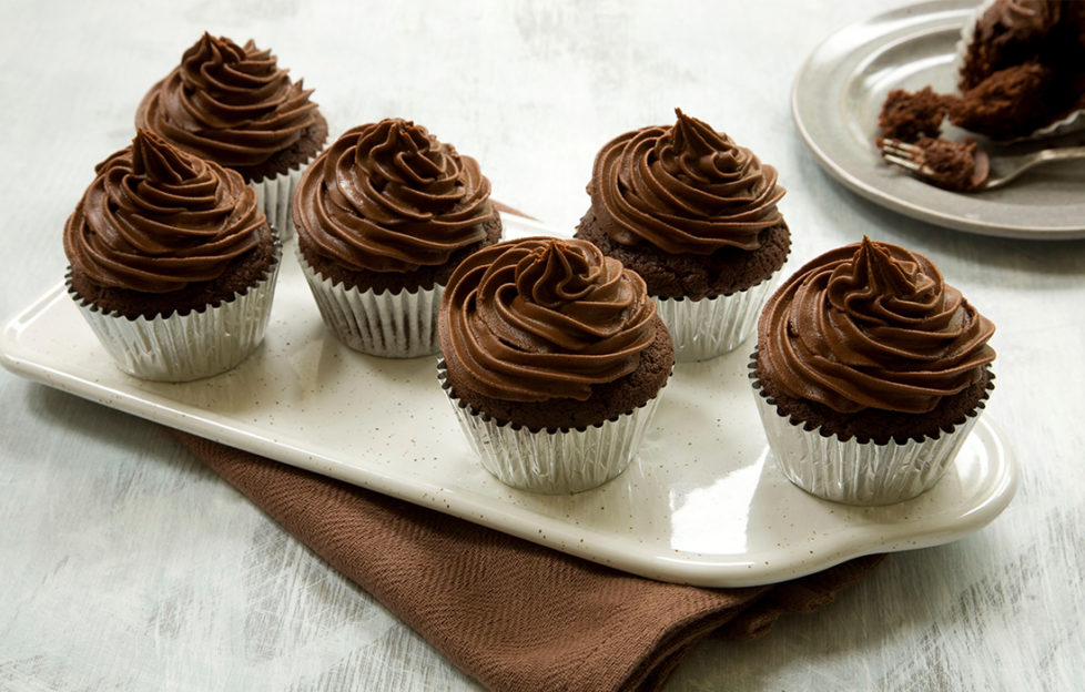 Six chocolate cupcakes on a white rectangular plate, all with large perfect swirls of chocolate fudge icing