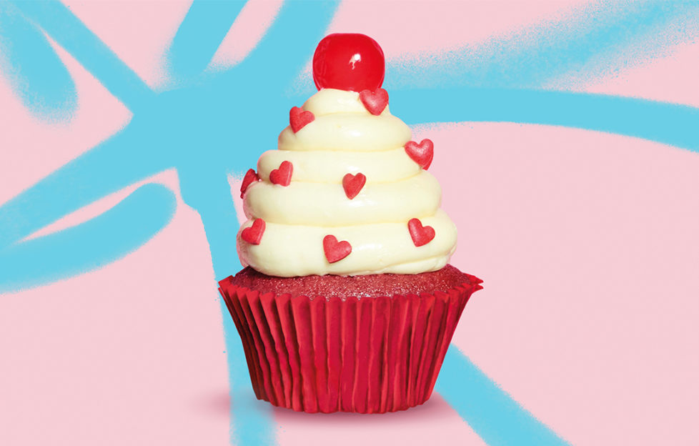 Red velvet cupcake with tower of white buttercream studded with tiny red sugar hearts and topped with a cherry, pink/blue background.