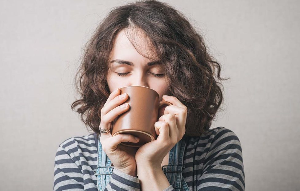 Woman drinking a cup of coffee or tea. Gray background