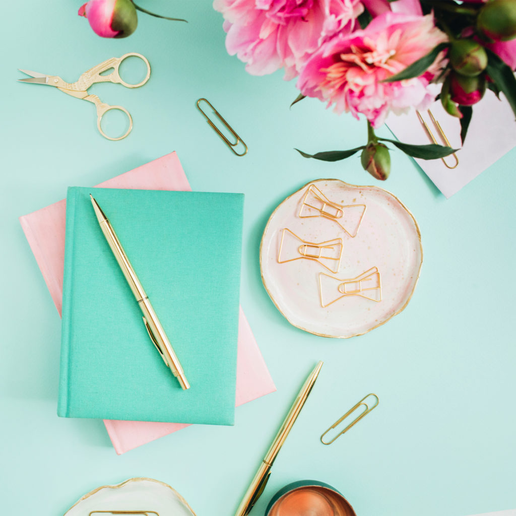 Turquoise diary on mint green table, pink peonies in a jar, golden pen, scrapbooking scissors and fancy paperclips nearby