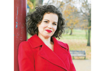Dr Philippa Kaye, dark haired woman in red coat with red lipstick in a park