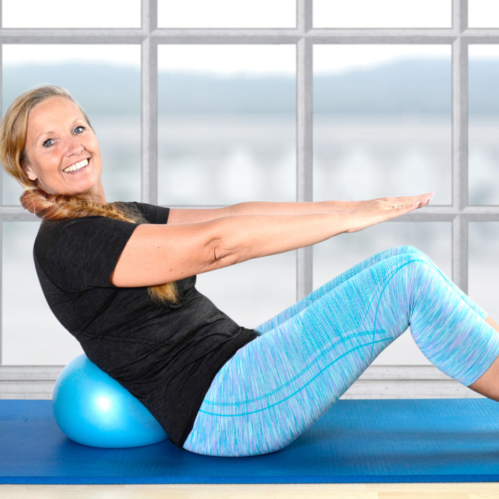 Happy woman doing sit ups with exercise ball supporting lower back