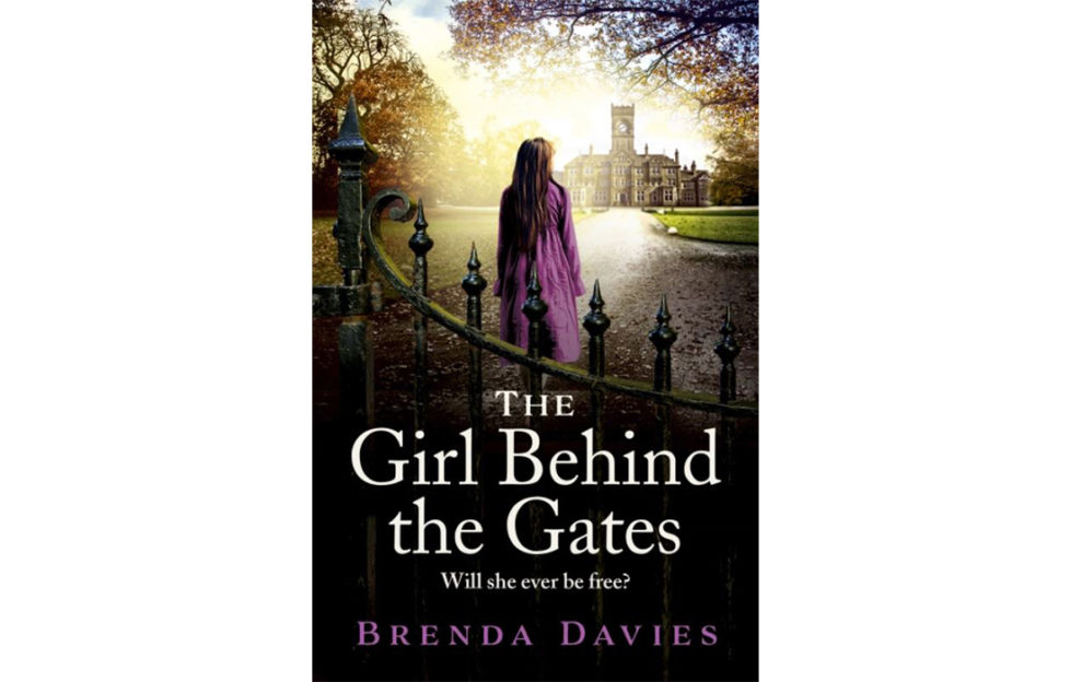 Cover of The Girl Behind The Gates, photo image of teenage girl in purple coat looking towards Victorian hospital building, mature trees around
