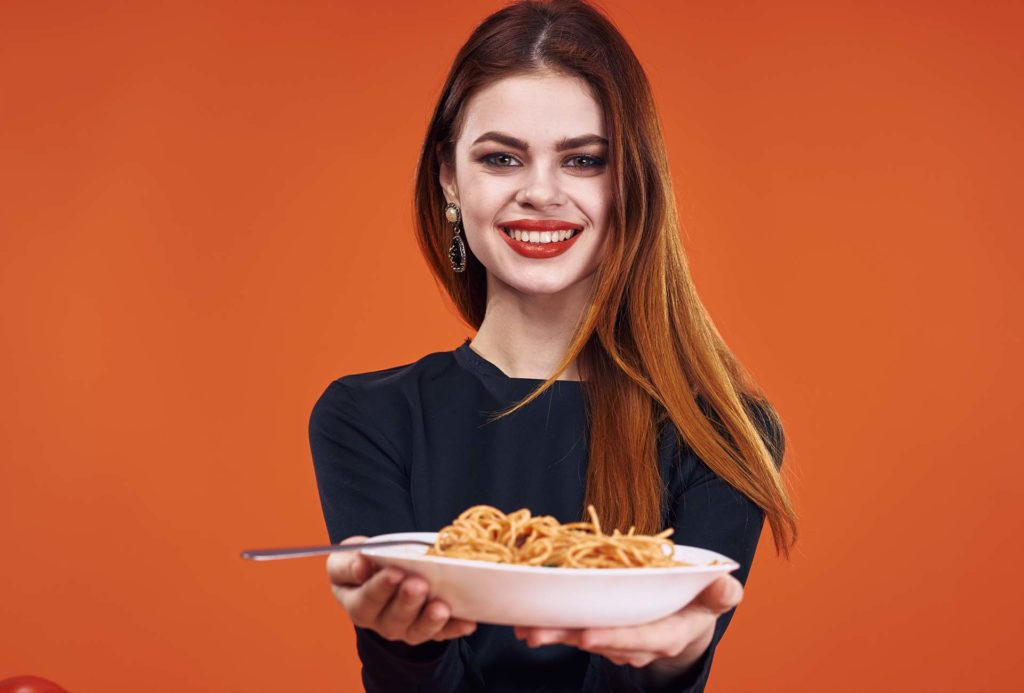 A smiling woman is holding a plate with spaghetti and on an orange background.