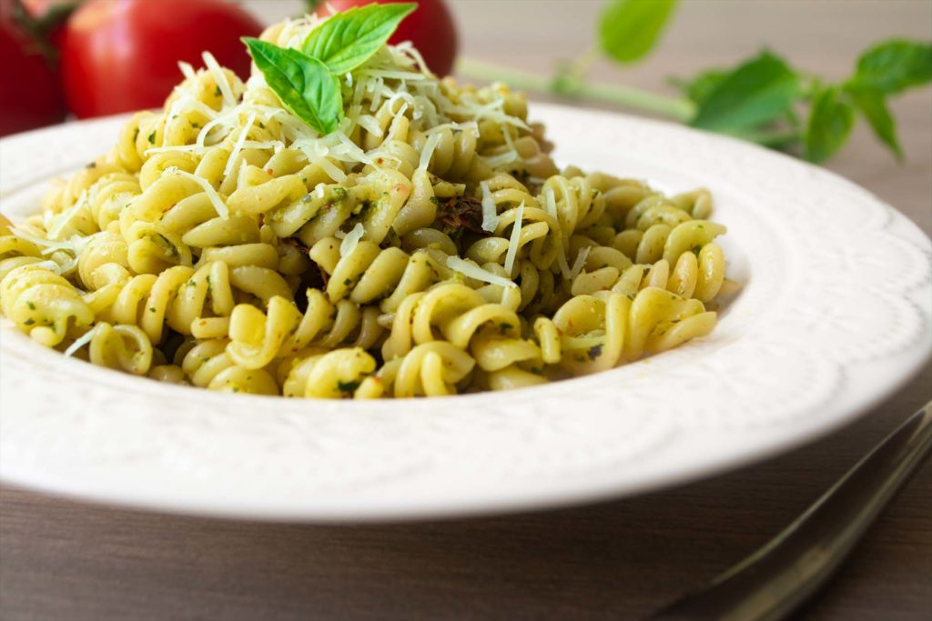Traditional Italian vegetarian pasta fusilli with fresh homemade basil and pine nut pesto sauce and topped with grated Parmesan cheese. Tomato, basil, parmesan cheese, napkin and fork in background
