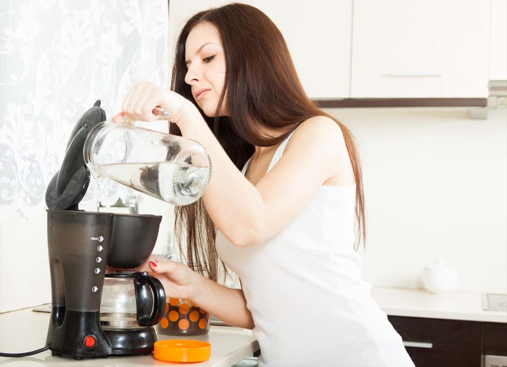Brunette in kitchen with coffee maker