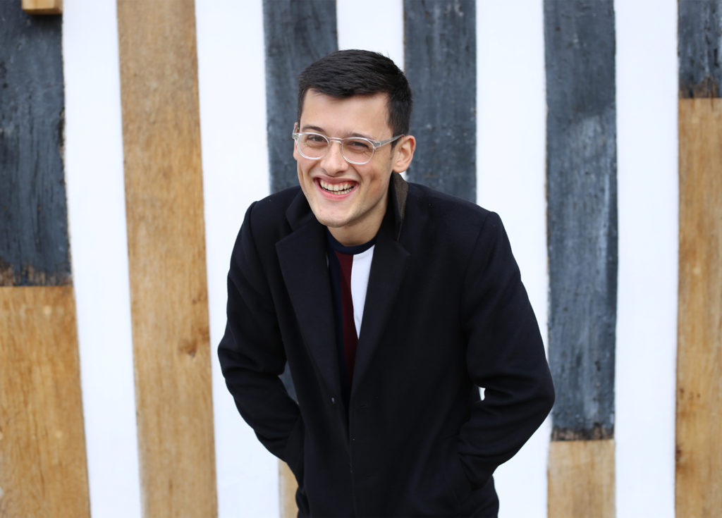 Bake Off contestant Michael Chakraverty, smiling, in a smart black jacket against white, blue and natural planks of wood
