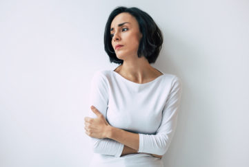 Woman in an anxious mood, arms wrapped around herself, looking to the side with sad expression, against plain white wall