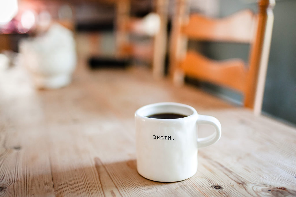 Mug of black coffee on wooden kitchen table. White mug has one word printed in black: Begin. Motivation for new career.