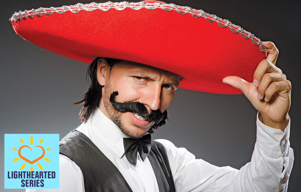 Man in red sombrero, bad fake Mexican moustache, bow tie and waistcoat, striking a pose