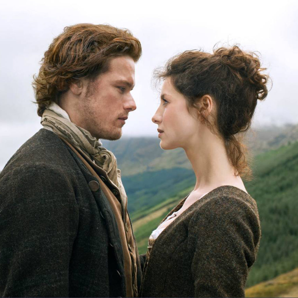 SAM HEUGHAN, CAITRIONA BALFE in OUTLANDER, beautiful misty Scottish hills behind