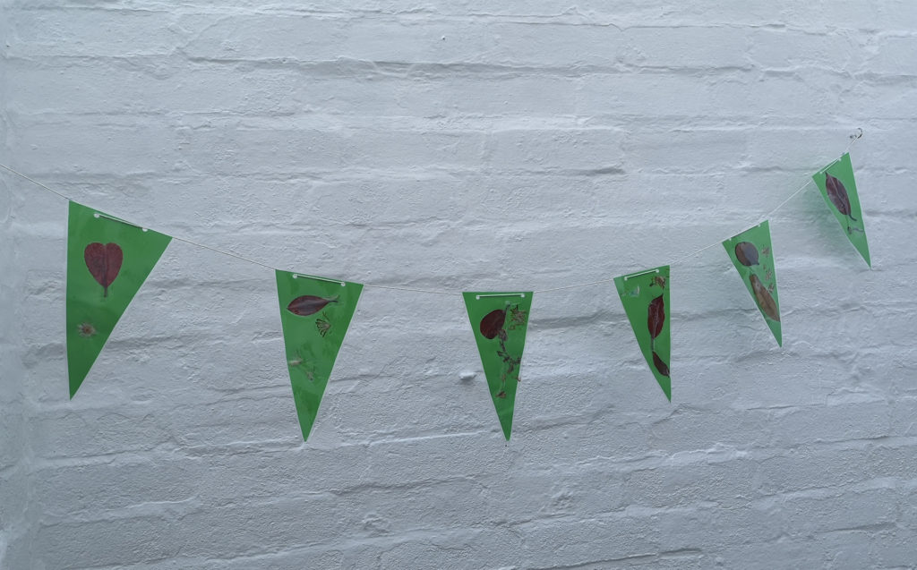 String of bunting hanging on white painted brick wall