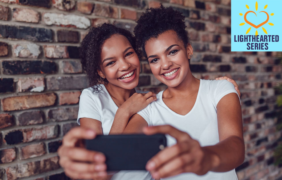 Two happy young girls in white v neck t shirts take photo of them together on a smartphone, against a brick wall