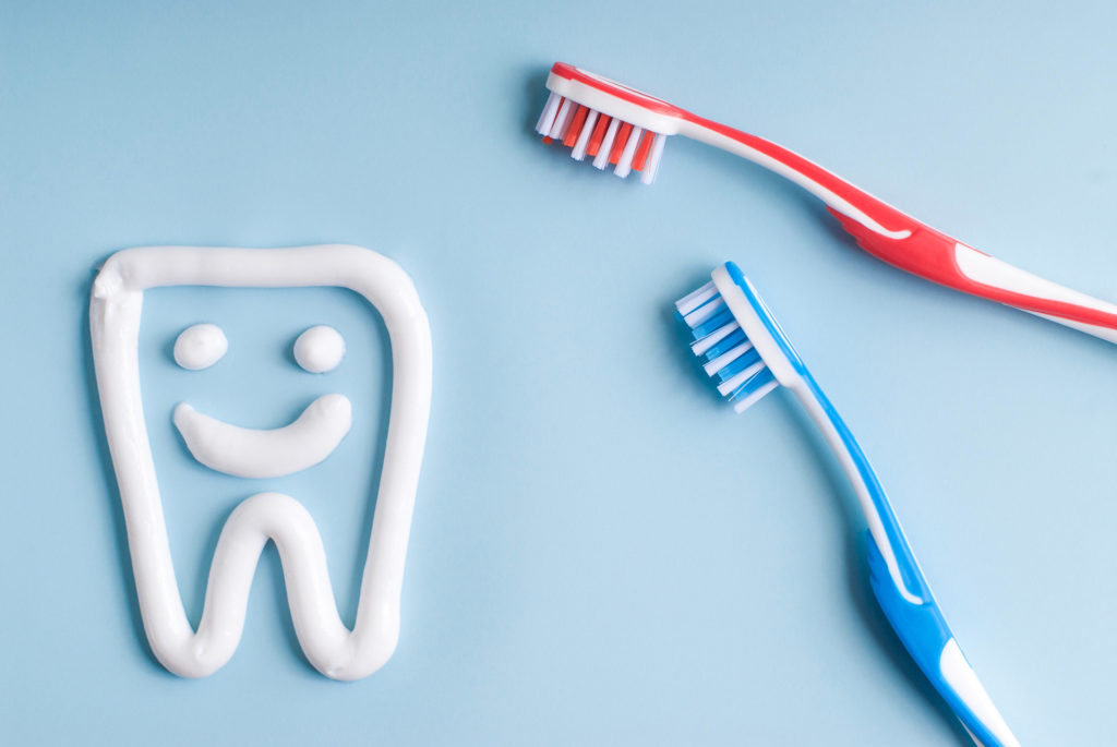 Toothpaste in a form of a smiling tooth. Red and blue toothbrushes. Toothpaste on blue. Dental hygiene.;