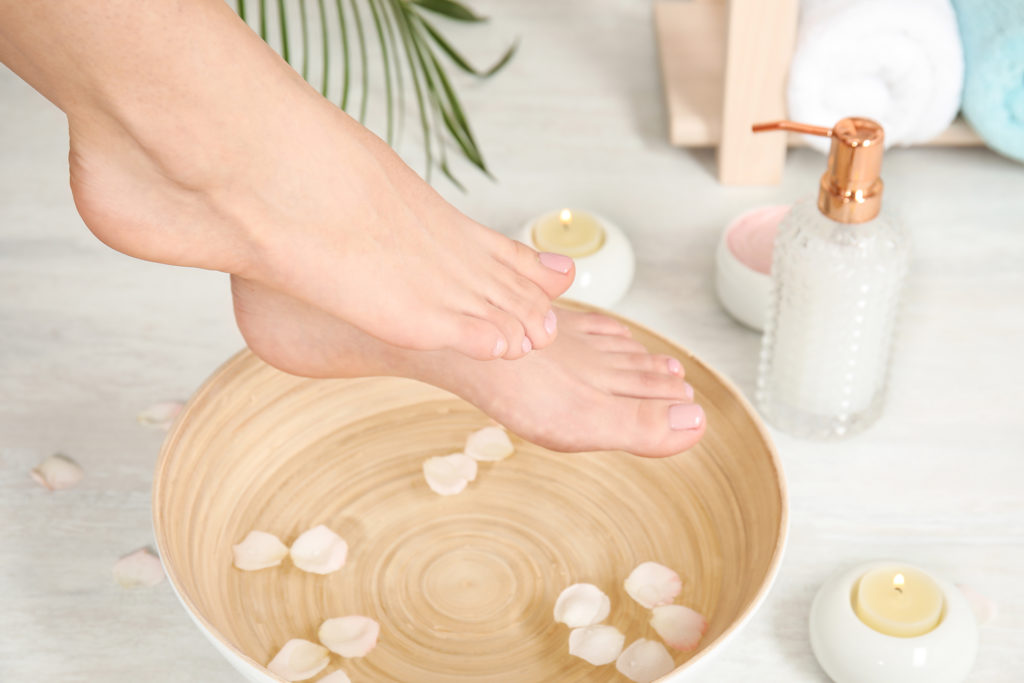 Woman putting her feet into bowl with water and rose petals indoors, closeup. Spa treatment;
