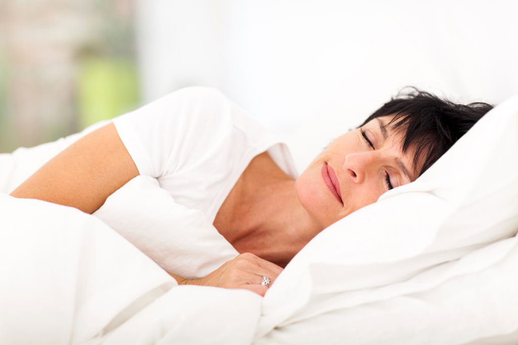 cute mature woman sleeping on bed;