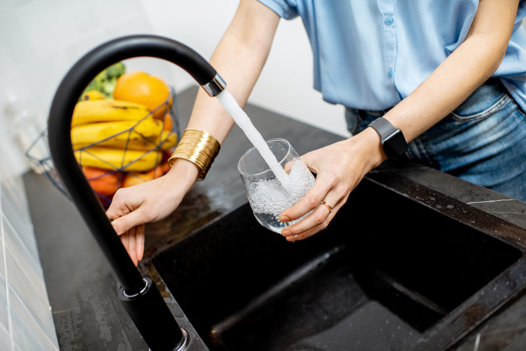 Woman filling glass with tap water for drinking on the kitchen;