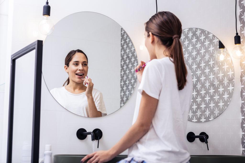 Circular mirror. Close up of appealing woman brushing teeth in front of circular mirror;