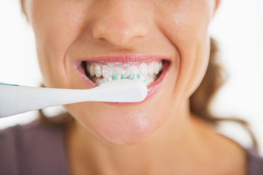 Closeup on happy woman brushing teeth;