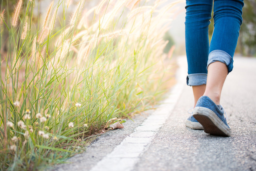 Pair of women's feet in trainers walking along edge of road