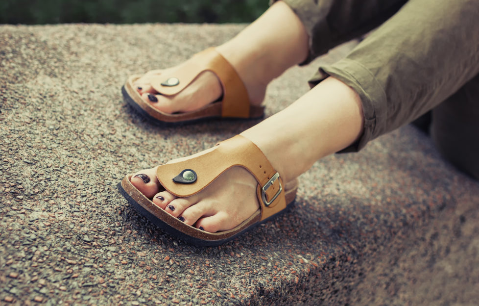 Woman's feet in yellow stylish summer sandals with dark nail polish, in green summer pants sitting on the wall;