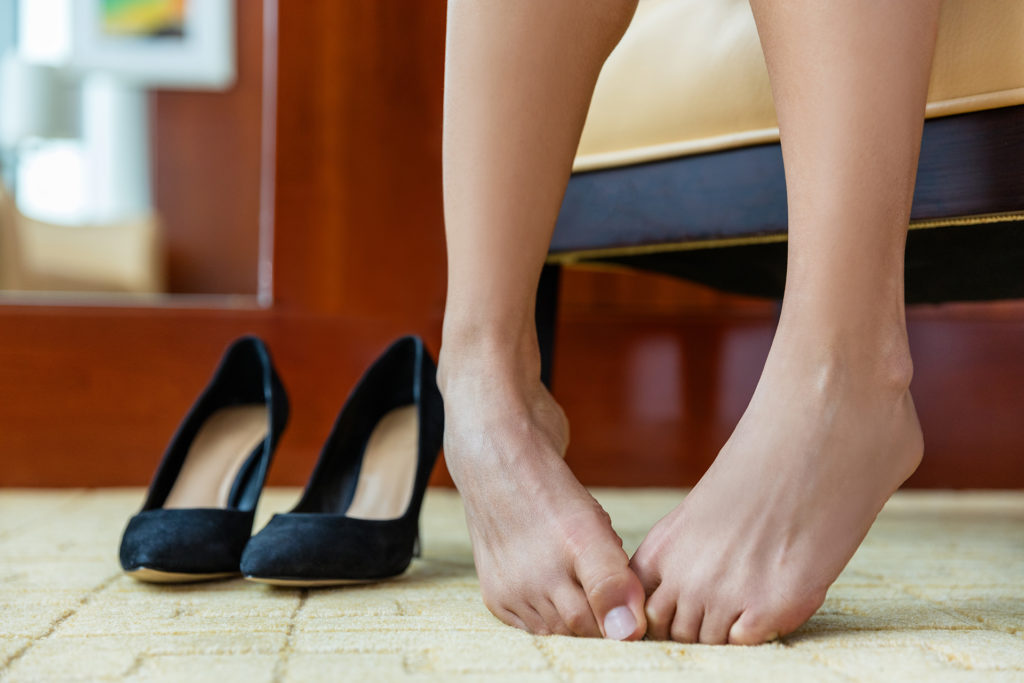 High heels shoe feet pain. Closeup of woman barefoot with painful toes has removed her formal stilettos at work or is embarrassed of foot problem, nails or in discomfort at shoe store or home.;