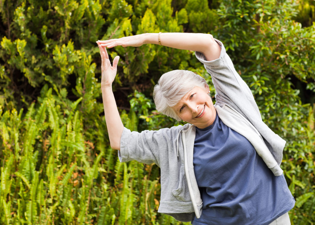 Mature woman doing her stretches in the garden;