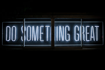 Neon sign, white capitals on black, reading Do Something Great. Career concept.