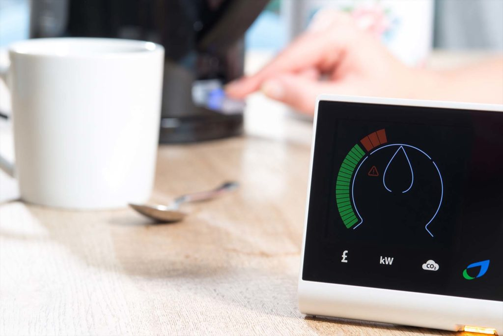 A smart meter is displayed on a wooden surface near mug and spoon and a kettle which is being switched on by a hand. The meter is giving a digital reading of energy consumption.
