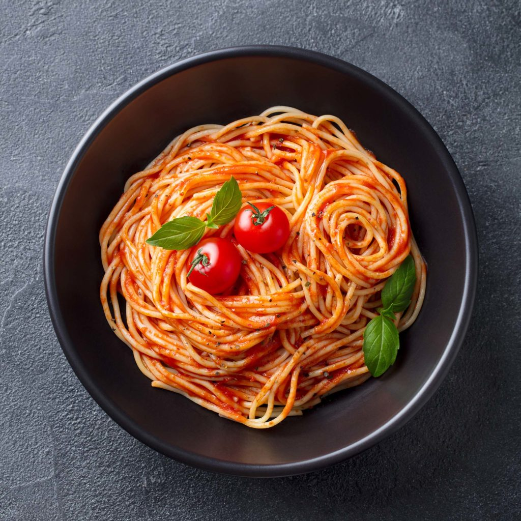 Pasta, spaghetti with tomato sauce in black bowl. Grey stone background. Top view. Close up.