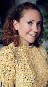 Niki Webster of Rebel Recipes, smiling young woman with curly brown hair wearing spotted yellow blouse