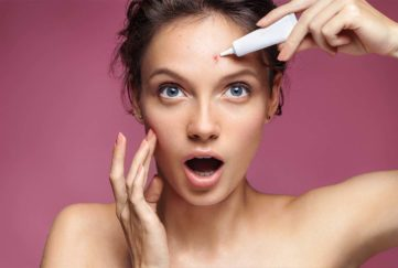 Young girl in shock of her acne. Photo of ugly girl with problem skin applying treatment cream on pink background. Skin care concept