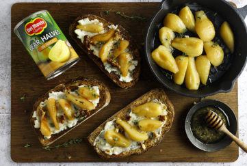 Pan of pears frying in butter, 3 slices of bread spread with blue cheese with pears and walnuts on top, and a can of Del Monte pear halves