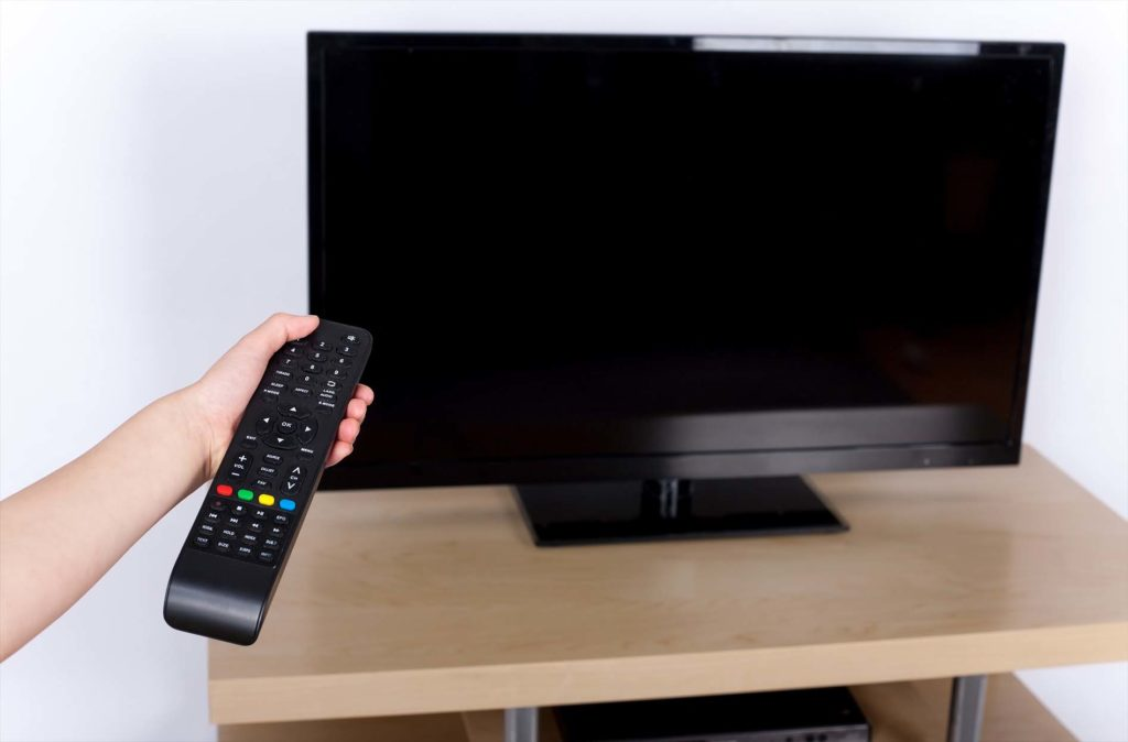 Hand turning off on the television with a remote control