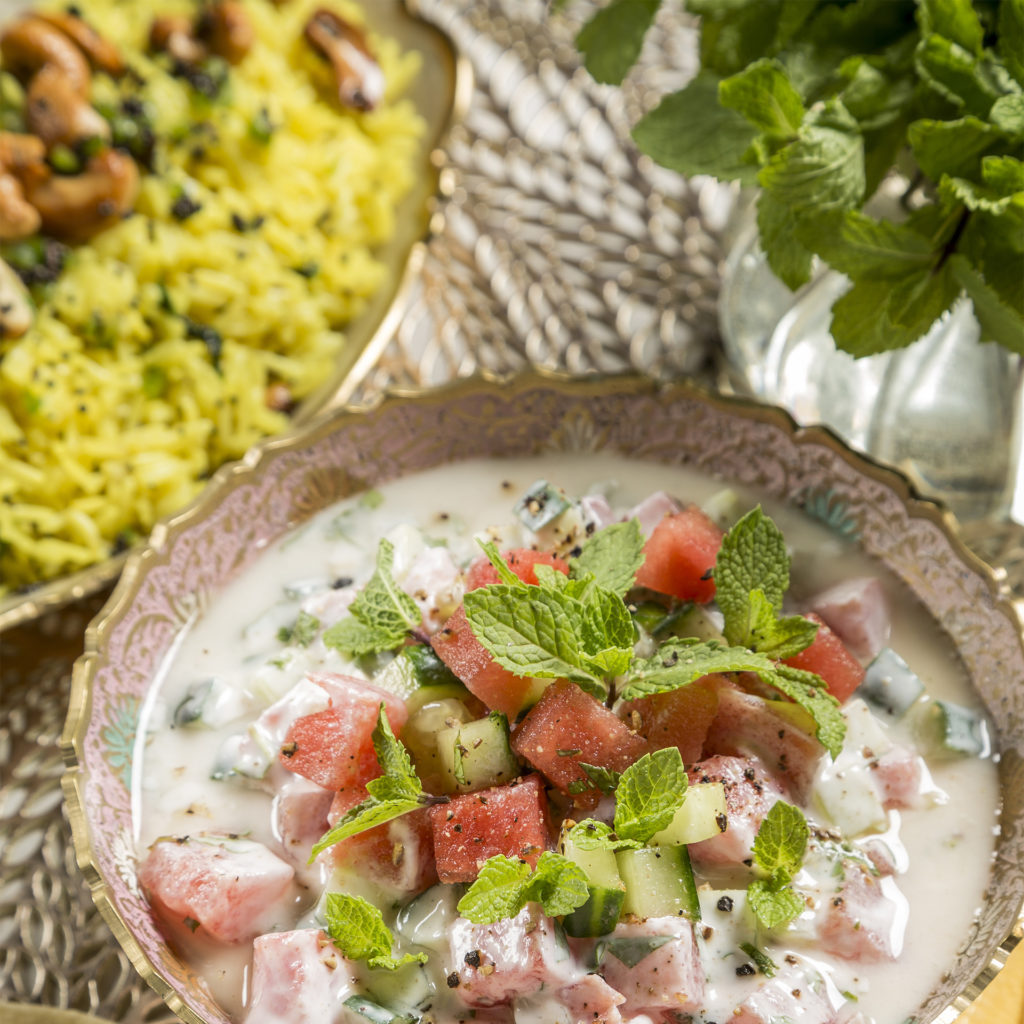 Bowl of watermelon, cucumber and mint in yogurt, and dish of yellow rice with roasted cashews and chopped herbs