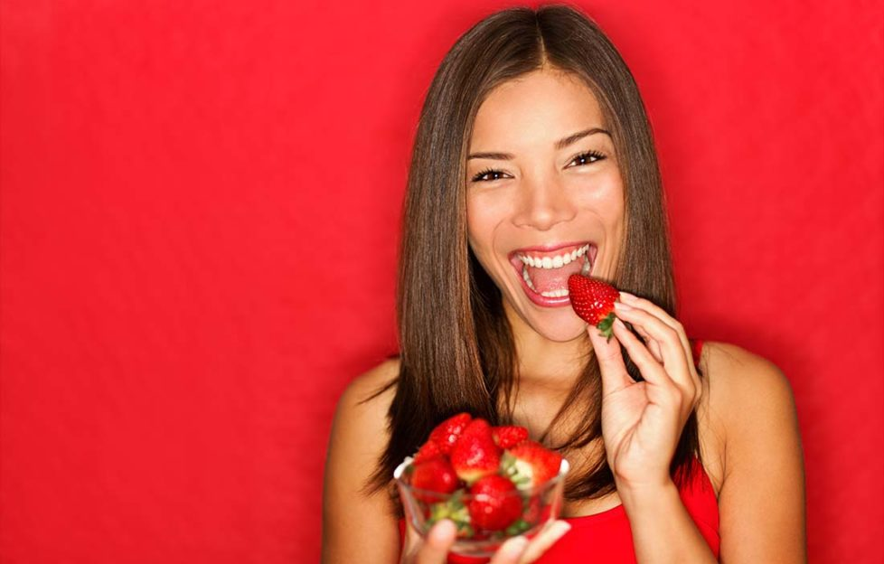 Woman eating strawberries happy. Pretty girl eating healthy snack on red background. Attractive Asian Caucasian female model joyful.