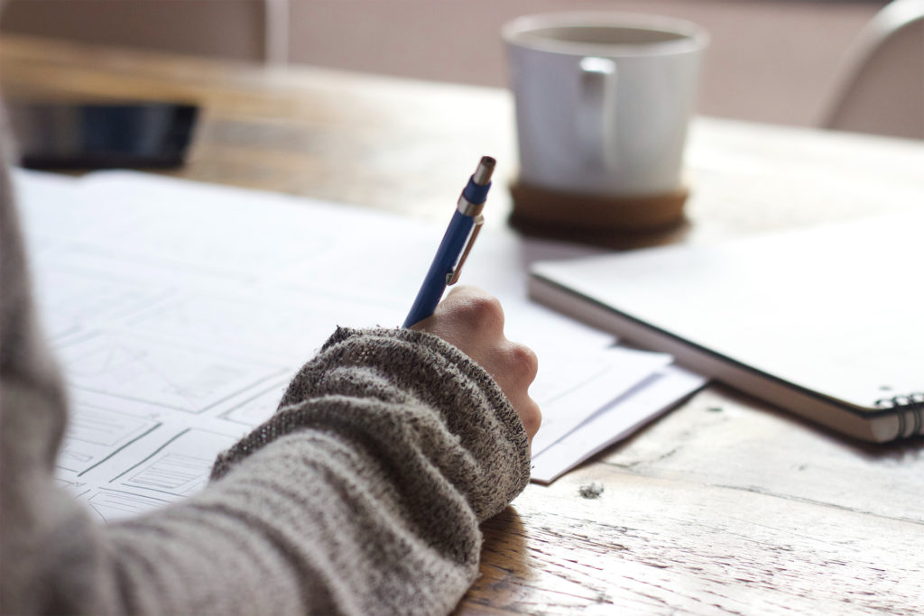 Woman in baggy brown jumper writing, a pile of written sheets under the one she is working on