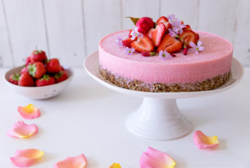 Yogurt cake, cheesecake-like dessert on a cake stand, crunchy base, creamy pink layer and topped with fresh strawberries