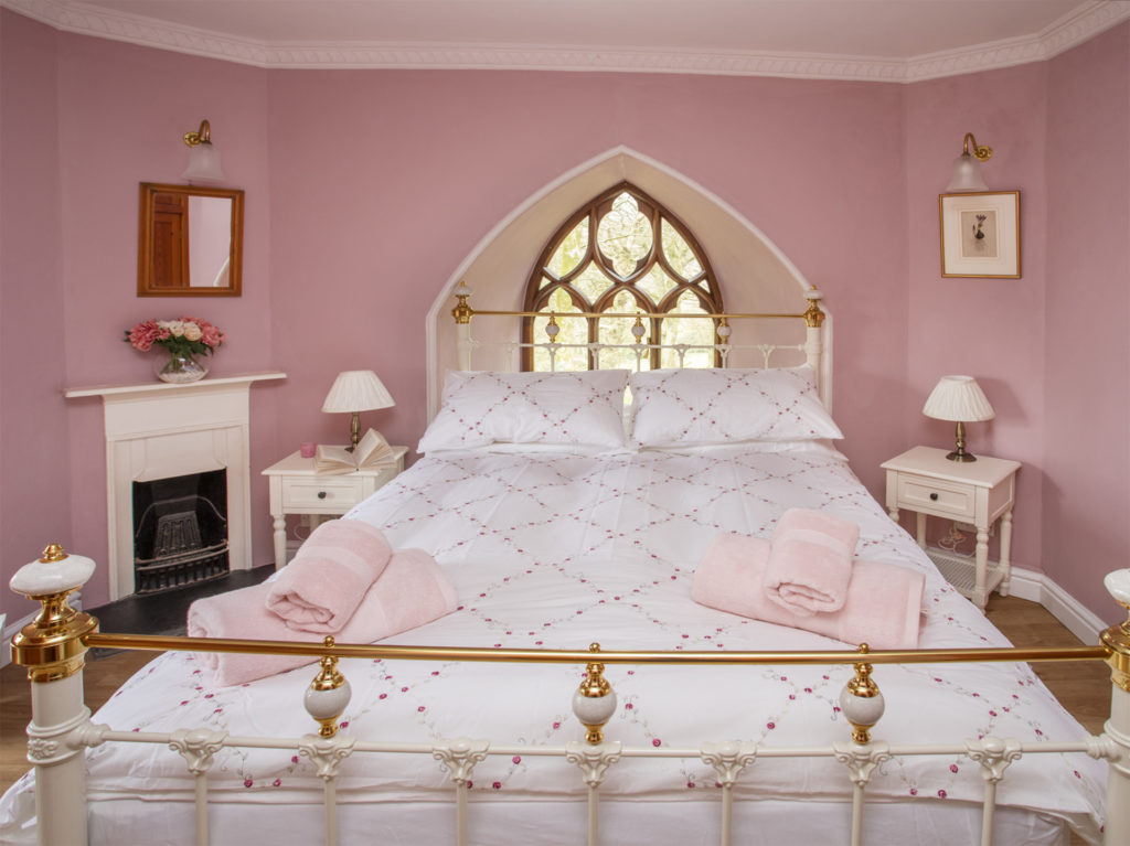Pink painted bedroom, Gothic pointed window in alcove behind bed head, double bed with brass frame and white covers, small fireplace
