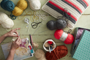 Crafter's desk with balls of yarn, scissors, pot of crochet hooks, crocheted cushion and woman's hands crocheting