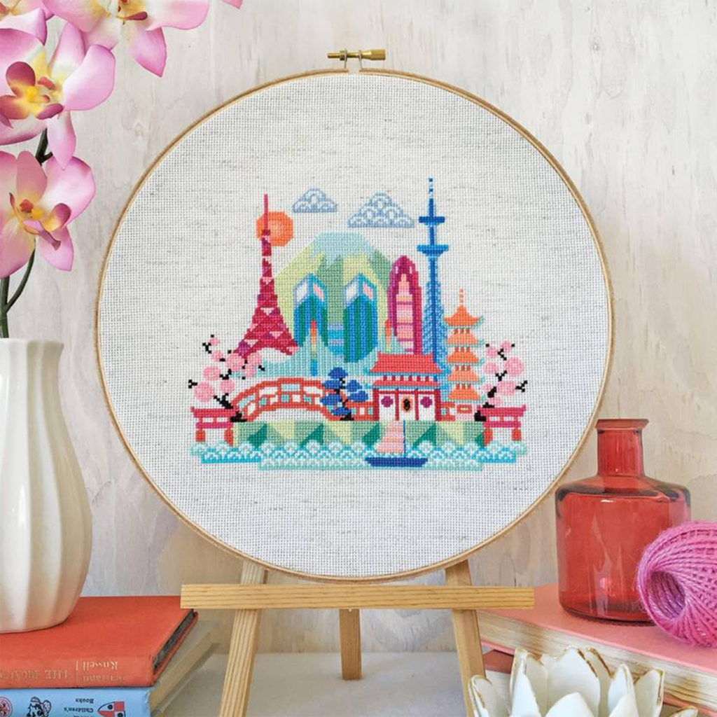 circular cross stitch frame with fairytale landscape of towers and bridges