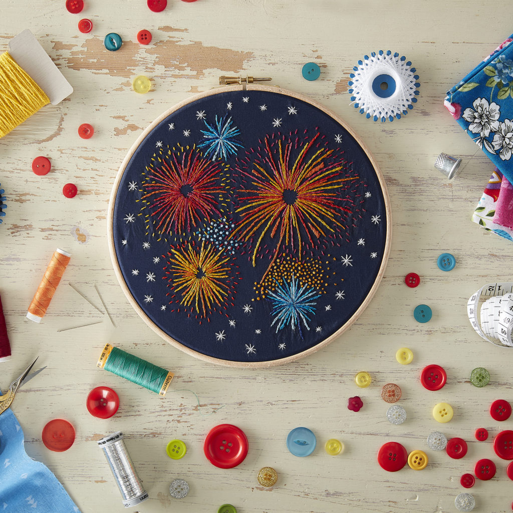 Small circular embroidery frame with black fabric and bright embroidery of fireworks, bright coloured buttons scattered on desk