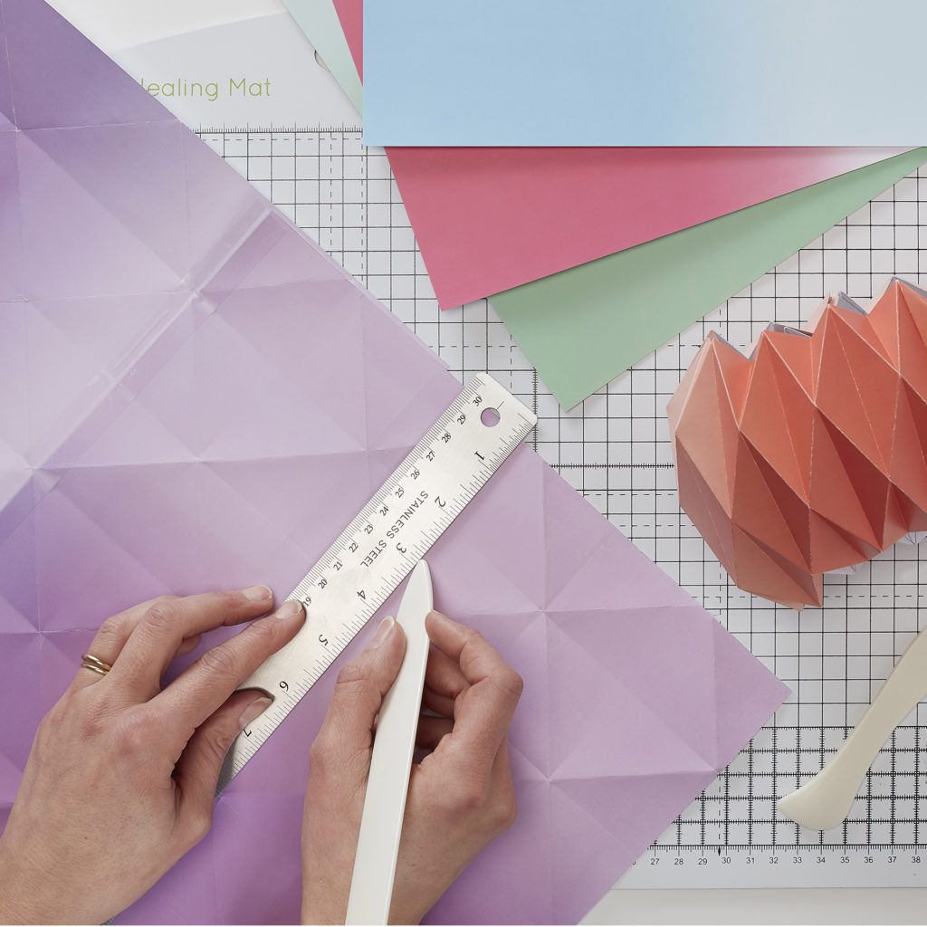 Person with metal ruler and scoring tool, sheets of coloured paper and a piece of honeycomb origami folding
