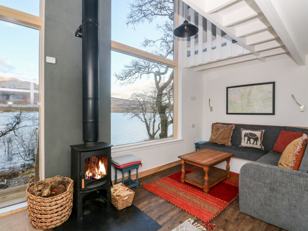 Modern log cabin with huge window and small woodburning stove with long pipe, red rug and tasteful sofas