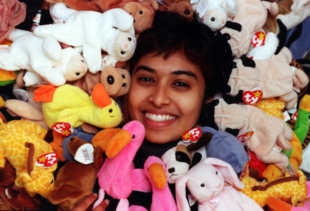 Young woman laughing, her face surrounded by Beanie Babies soft toys including a bright pink flamingo and yellow duck