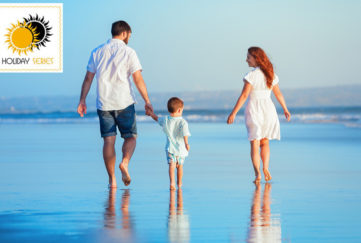 Mum, dad and small boy walking along edge of the sea. Boy holding dad's hand, mum reaching her hand out to him