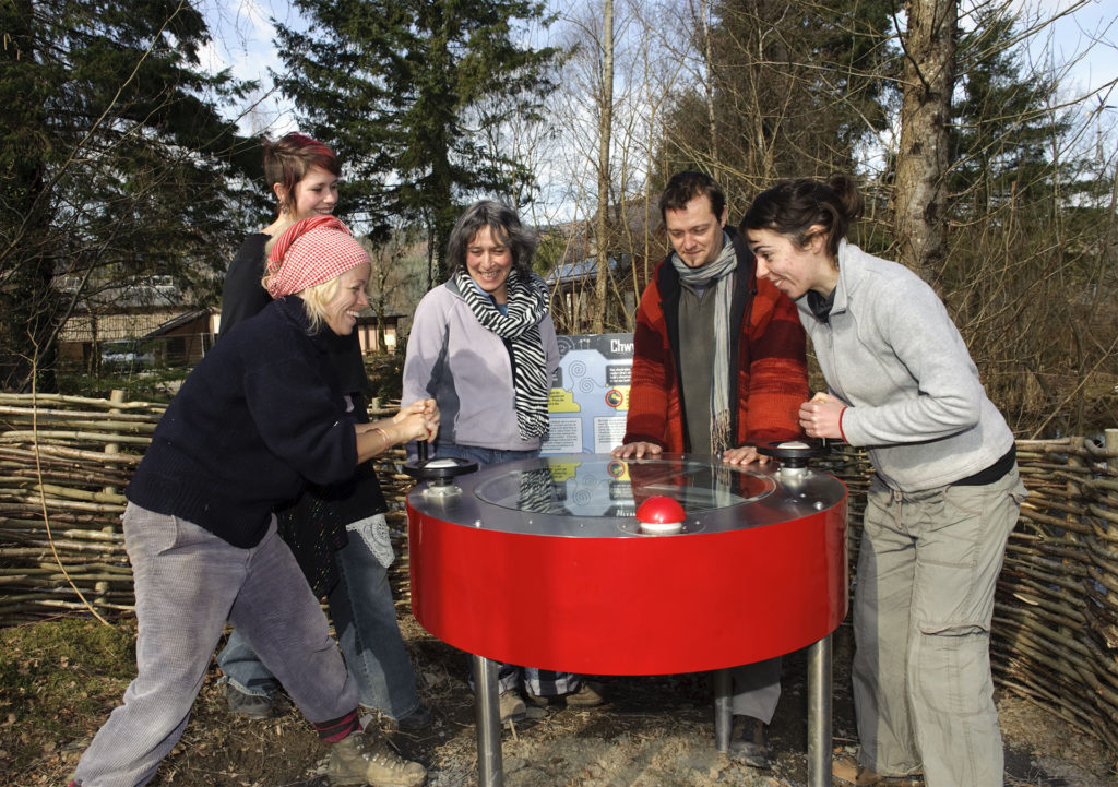 5 people laughing as they turn handles on a red drum shaped gadget, woodland and willow panels behind
